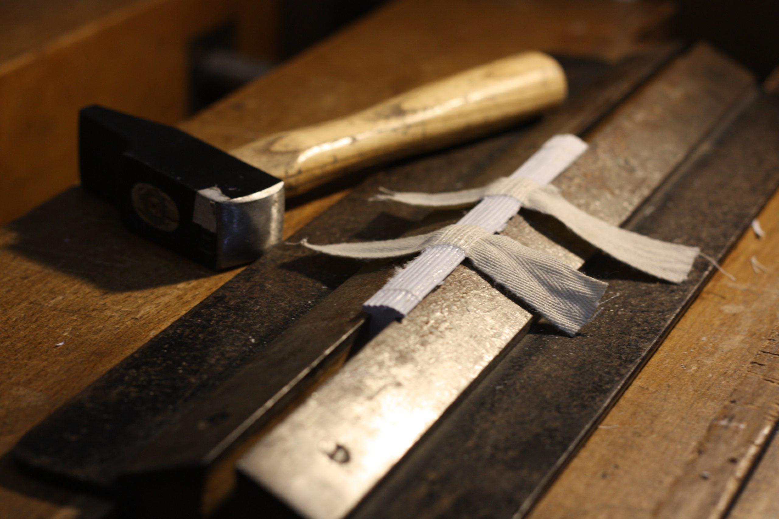 Le livre est placé dans un étau pour être endossé avec un marteau